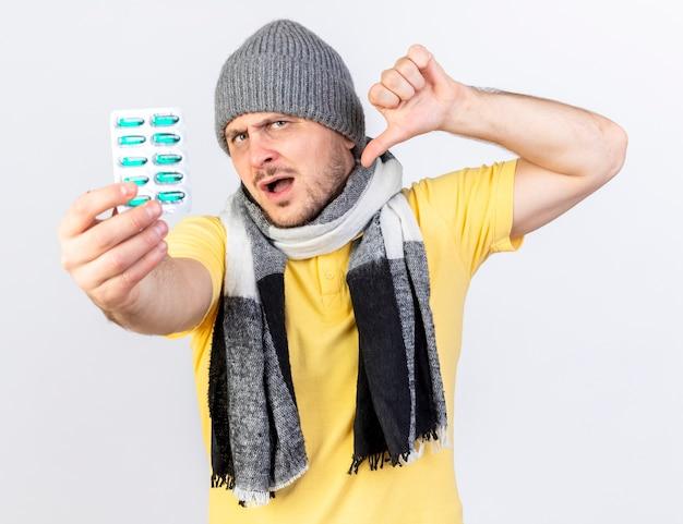 겨울 모자와 스카프를 착용하고 불쾌한 젊은 금발의 아픈 슬라브 남자는 아래로 엄지 손가락과 복사 공간이 흰 벽에 고립 된 의료 약의 팩을 보유