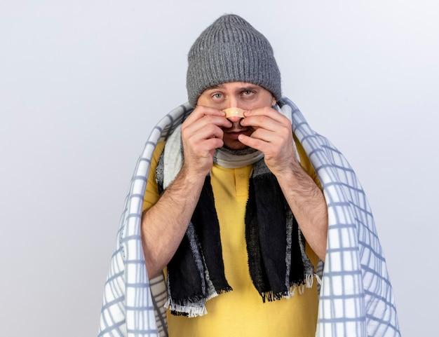 격자 무늬에 싸여 겨울 모자와 스카프를 착용하는 불쾌한 젊은 금발의 아픈 슬라브 남자는 복사 공간이 흰 벽에 고립 된 코에 의료 석고를 넣습니다.