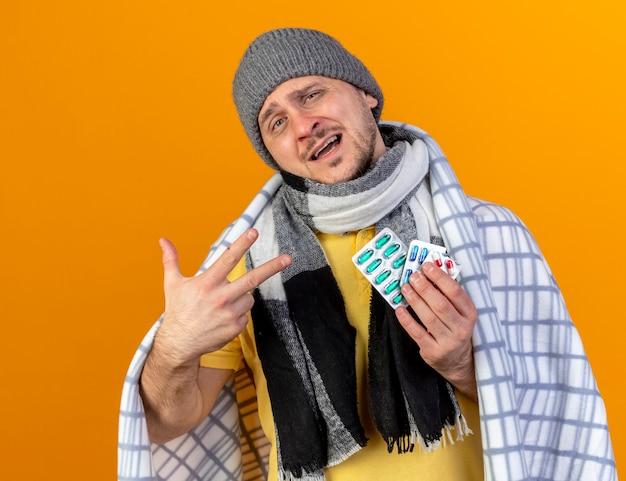 겨울 모자와 스카프를 착용하는 불쾌한 젊은 금발의 아픈 슬라브 남자