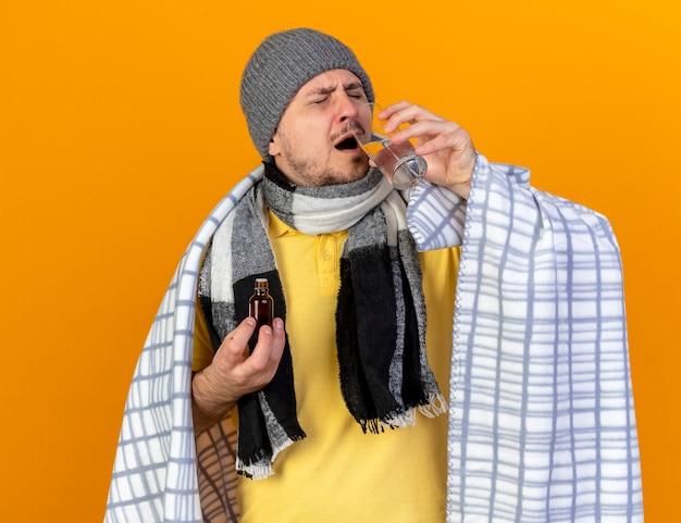 冬の帽子とスカーフを身に着けている不機嫌な若い金髪の病気のスラブ人