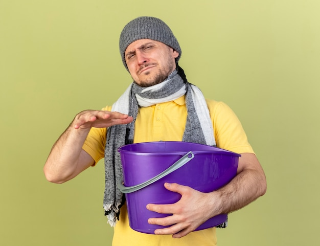 Unpleased young blonde ill slavic man wearing winter hat and scarf holds hand over plastic bucket isolated on olive green wall with copy space