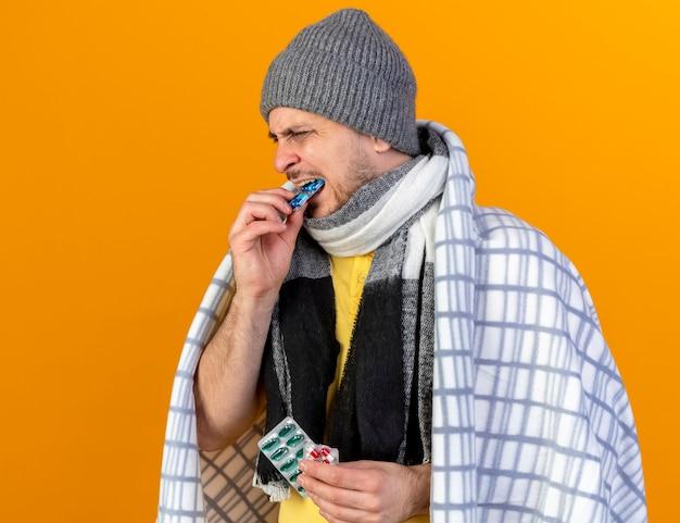 Il giovane uomo slavo malato biondo dispiaciuto che indossa il cappello e la sciarpa di inverno avvolti in plaid tiene e finge di mordere il pacchetto delle pillole mediche isolate sulla parete arancione con lo spazio della copia