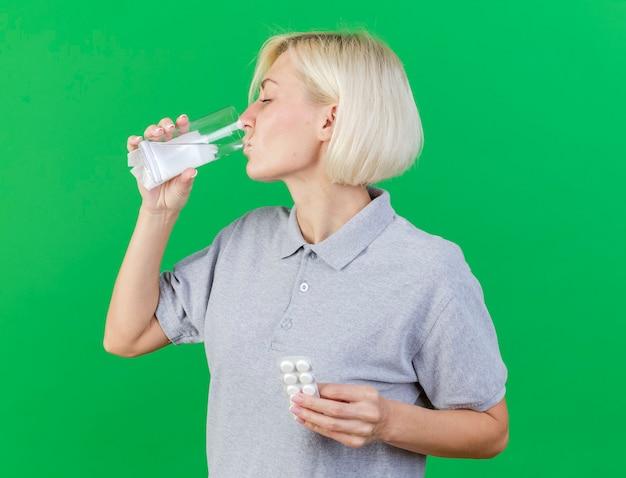 La giovane donna slava malata bionda sgradevole beve il bicchiere d'acqua e tiene il pacchetto di pillole mediche isolato sulla parete verde con lo spazio della copia