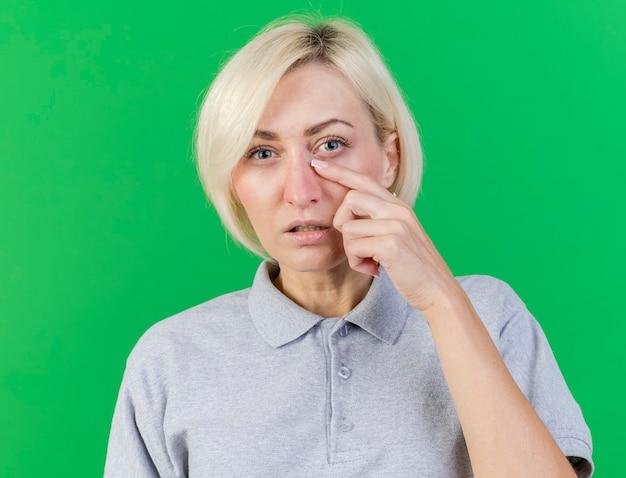 Недовольная молодая блондинка больная славянская женщина кладет палец на веко, изолированное на зеленом