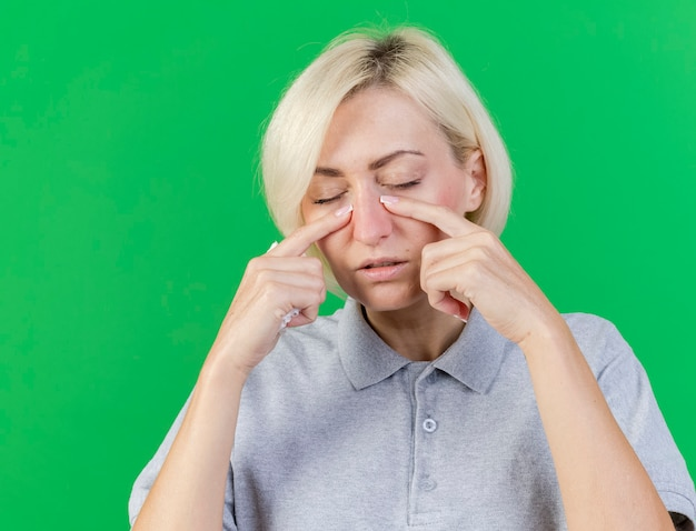 Недовольная молодая блондинка больная славянская женщина кладет пальцы на веко