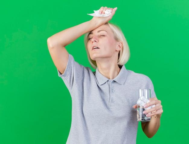 不機嫌な若い金髪の病気のスラブ女性が額に手を置き、コピースペースで緑の壁に隔離された水のガラスと医療薬のパックを保持します