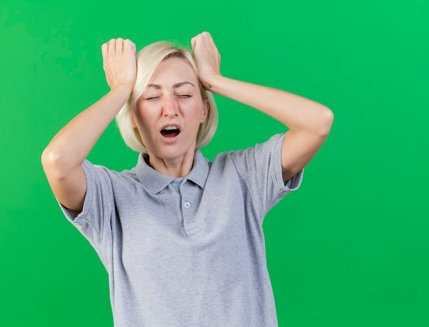 불쾌한 젊은 금발의 아픈 슬라브 여자가 이마에 손을 넣습니다.