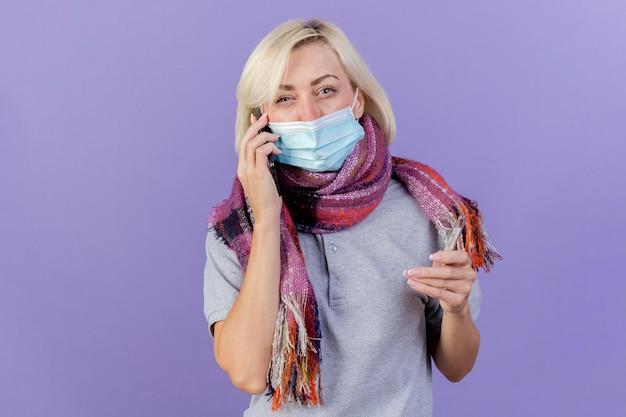 Giovane donna slava malata bionda dispiaciuta che indossa sciarpa e maschera medica