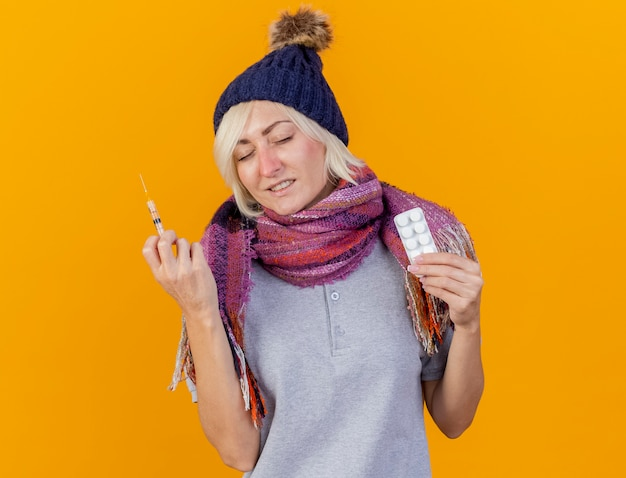 冬の帽子とスカーフを身に着けている不機嫌な若い金髪の病気のスラブ女性は、コピースペースでオレンジ色の壁に分離された注射器と医療薬のパックを保持します