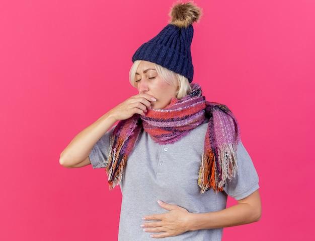 冬の帽子とスカーフを身に着けている不機嫌な若いブロンドの病気のスラブ女性は口に手を置きます