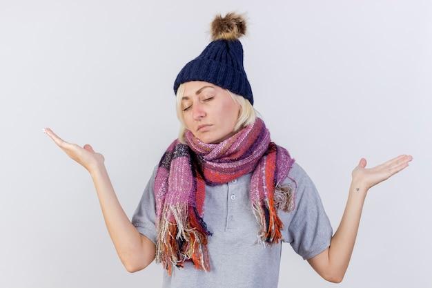 冬の帽子とスカーフを身に着けている不機嫌な若いブロンドの病気のスラブ女性は、コピースペースで白い壁に隔離された手を開いて立っています