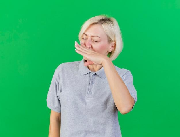 불쾌한 젊은 금발의 아픈 슬라브 여자 복사 공간이 녹색 벽에 고립 된 손으로 코를 닦아