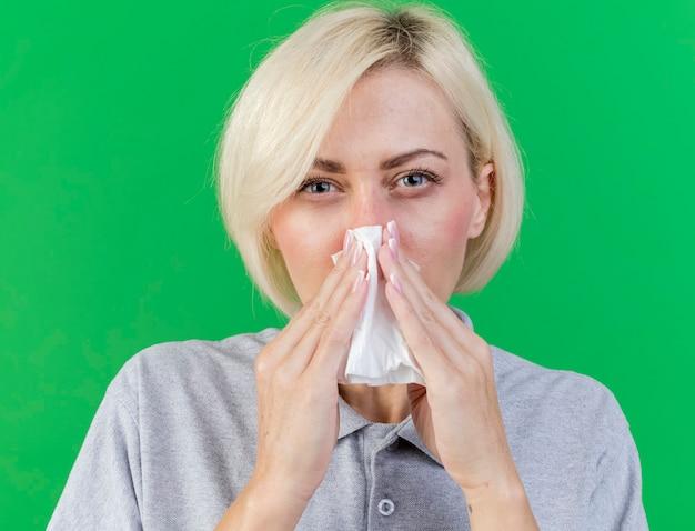 不機嫌な若いブロンドの病気のスラブ女性は、コピースペースで緑の壁に分離されたティッシュで鼻を拭きます