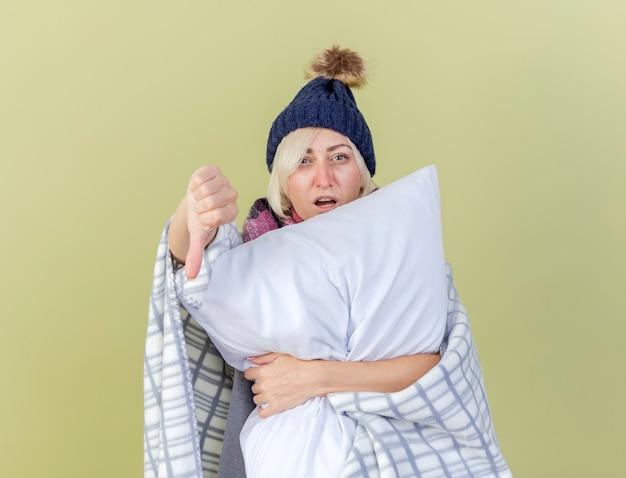 Giovane donna bionda malata dispiaciuta che indossa cappello invernale e sciarpa avvolta in plaid pollici verso il basso e tiene il cuscino isolato sulla parete verde oliva