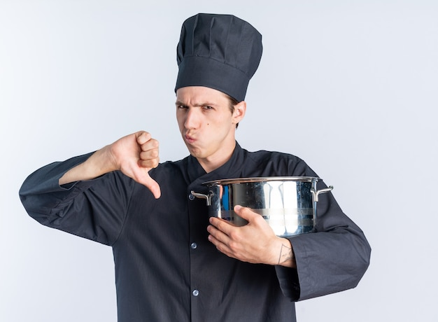Недовольный молодой блондин мужчина-повар в униформе шеф-повара и кепке, держащей горшок, смотрит в камеру, показывая большой палец вниз, изолированный на белой стене