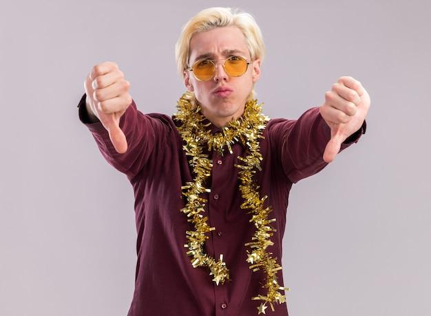 Недовольный молодой блондин в очках с гирляндой из мишуры на шее, глядя в камеру, показывает палец вниз на белом фоне