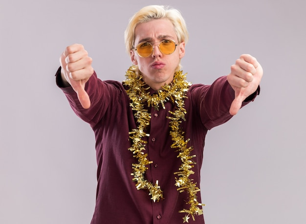 Unpleased young blonde man wearing glasses with tinsel garland around neck looking at camera showing thumbs down isolated on white background
