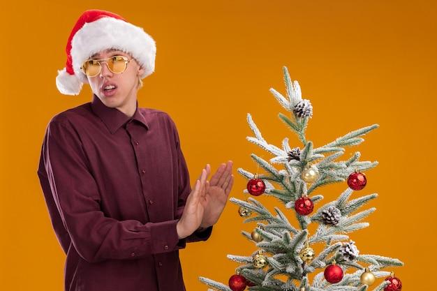 Недовольный молодой блондин в шляпе санта-клауса и очках, стоя возле украшенной елки, глядя в сторону, делая отказный жест, изолированный на оранжевом фоне