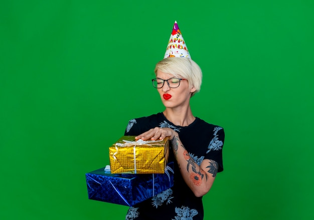 Unpleased young blonde party girl wearing glasses and birthday cap holding gift boxes with closed eyes isolated on green background with copy space