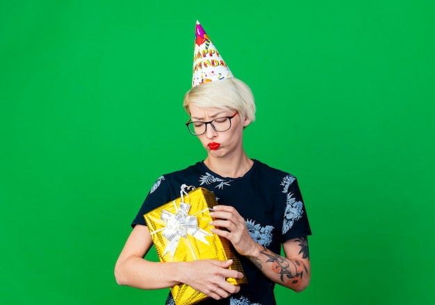 Felice giovane bionda party girl con gli occhiali e cappello di compleanno holding e guardando la confezione regalo isolato su sfondo verde con spazio di copia