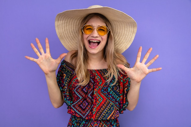 Unpleased young blonde slavic girl with sunglasses and with sun hat standing with raised hands