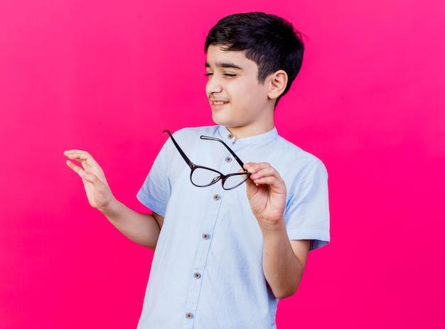 コピースペースのあるピンクの壁に孤立していない身振りで目を閉じて手を空中に保持している眼鏡を持っている不機嫌な少年