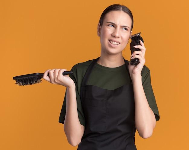 制服を着た不機嫌な若いブルネットの理髪師の女の子は、オレンジ色の側面を見てバリカンと櫛を保持します