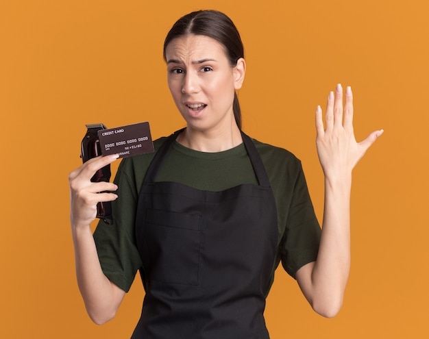 Недовольная молодая брюнетка-парикмахер в униформе держит руку открытой и держит машинку для стрижки волос с кредитной картой на оранжевом