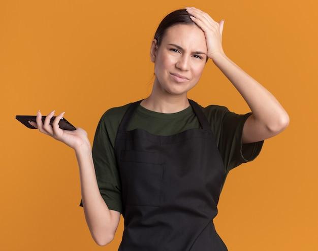 제복을 입은 불쾌한 젊은 갈색 머리 이발사 소녀가 이마에 손을 대고 머리 깎기를 보유하고 있습니다.