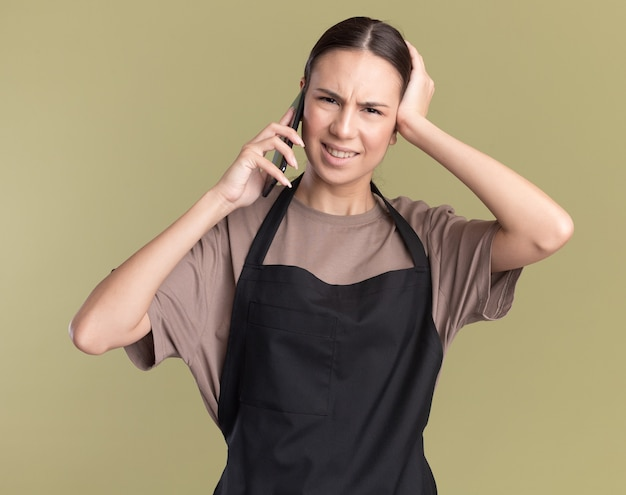 제복을 입은 불쾌한 젊은 갈색 머리 이발사 소녀가 머리에 손을 대고 올리브 그린에 전화로 이야기합니다.