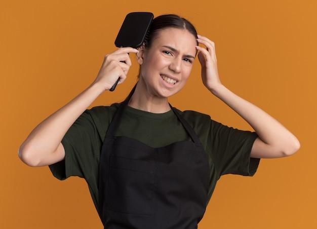 Giovane ragazza bruna scontenta del barbiere in uniforme che pettina i capelli isolati sulla parete arancione con lo spazio della copia