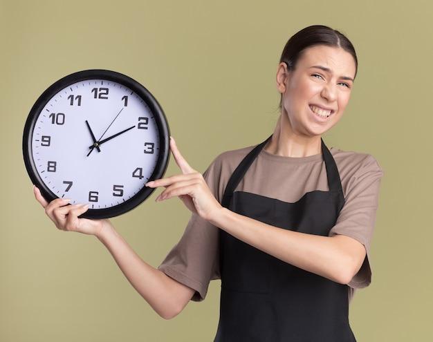 La giovane ragazza castana del barbiere in uniforme tiene l'orologio su verde oliva