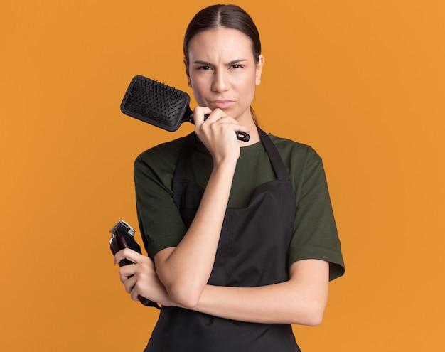 Una giovane barbiere bruna scontenta in uniforme tiene in mano tagliacapelli e pettine