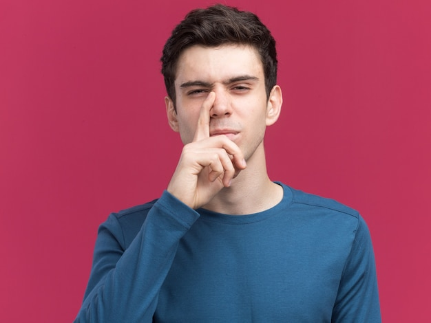 不機嫌な若いブルネットの白人の少年はピンクの鼻に指を置きます