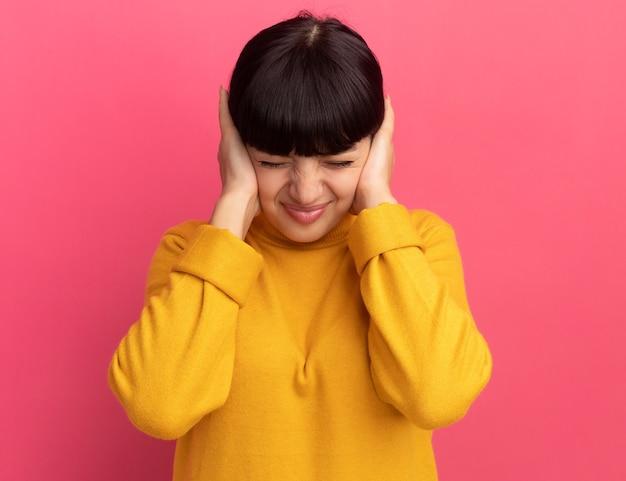 La giovane ragazza caucasica castana dispiaciuta chiude le orecchie con le mani sul colore rosa