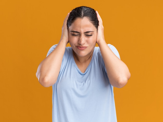 Unpleased young brunette caucasian girl covers ears with hands isolated on orange wall with copy space