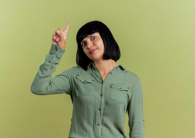 La giovane ragazza caucasica castana dispiaciuta indica in su che esamina macchina fotografica isolata su fondo verde oliva con lo spazio della copia