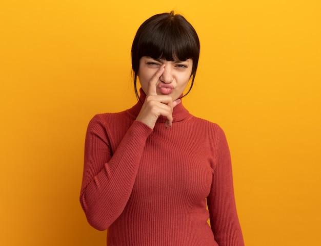 La giovane ragazza caucasica castana scontenta mette il dito sul naso isolato sulla parete arancione con lo spazio della copia