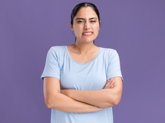 Unpleased young brunette caucasian girl standing with crossed arms isolated on purple wall with copy space