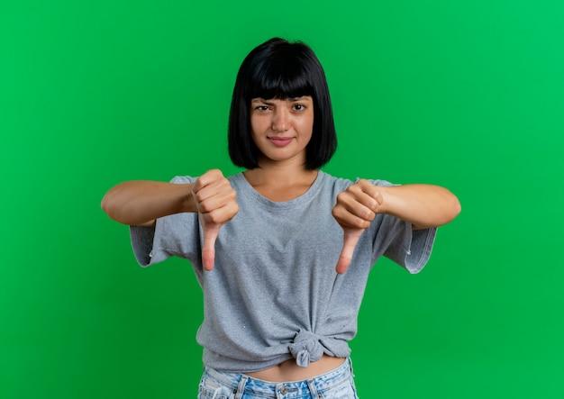 불쾌한 젊은 갈색 머리 백인 여자 복사 공간이 녹색 배경에 고립 된 두 손으로 아래로 엄지 손가락