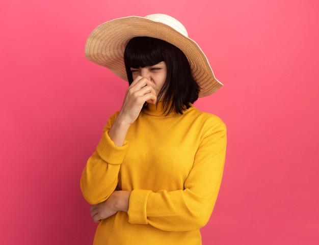 ビーチの帽子をかぶって不機嫌な若いブルネットの白人の女の子は鼻を保持します