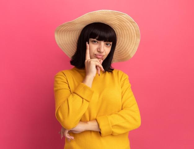 Il cappello da portare della spiaggia da portare della ragazza caucasica castana giovane insoddisfatta mette la mano sul mento e guarda la macchina fotografica sul rosa