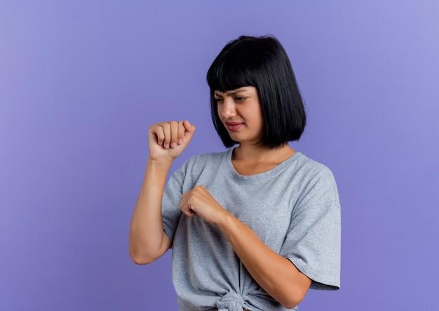 La giovane donna caucasica castana dispiaciuta mantiene i pugni che esaminano il lato isolato su fondo viola con lo spazio della copia
