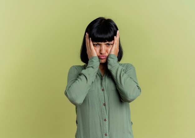 La giovane donna caucasica castana insoddisfatta mette le mani sul viso isolato su sfondo verde oliva con spazio di copia