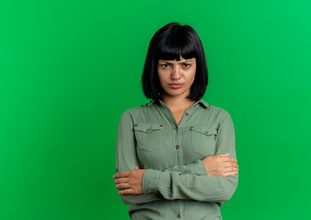 Unpleased young brunette caucasian woman stands with crossed arms isolated on green background with copy space
