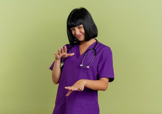 聴診器と制服を着た不機嫌な若いブルネットの女性医師は、コピースペースでオリーブグリーンの背景に手をまっすぐに隔離します