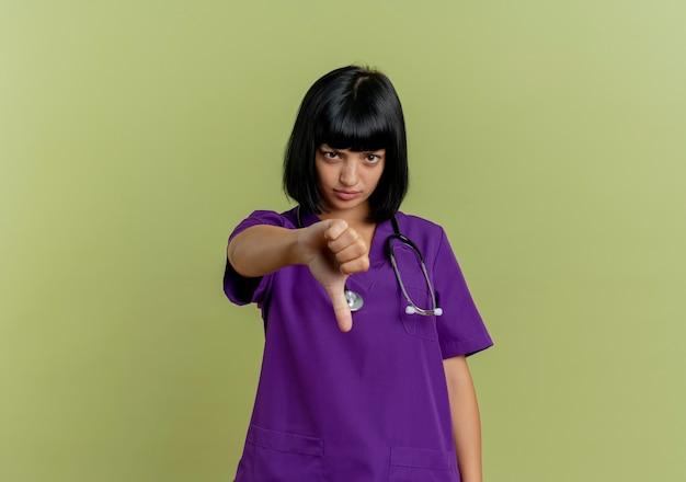 Недовольная молодая брюнетка женщина-врач в униформе со стетоскопом показывает палец вниз на оливково-зеленом фоне с копией пространства