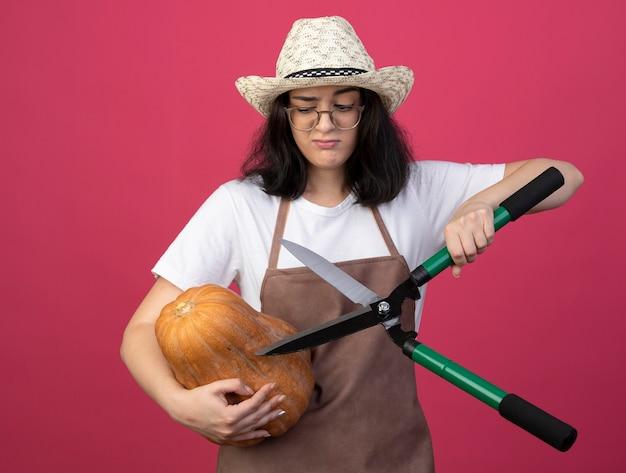 Недовольная молодая брюнетка женщина-садовник в оптических очках и в униформе в садовой шляпе держит садовые ножницы и тыкву, изолированную на розовой стене