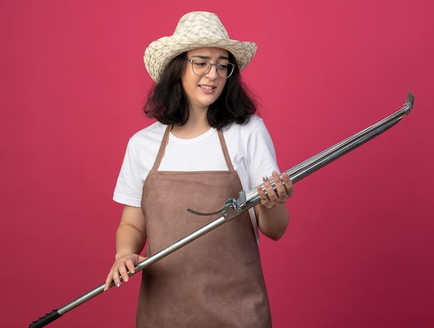 Il giardiniere femminile giovane brunetta dispiaciuto in vetri ottici e in uniforme che indossa il cappello da giardinaggio tiene il rastrello del foglio isolato sulla parete rosa