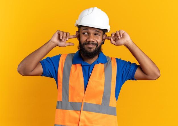 コピースペースでオレンジ色の壁に隔離された側を見て指で彼の耳を閉じる安全ヘルメットと制服を着た不機嫌な若いビルダー男